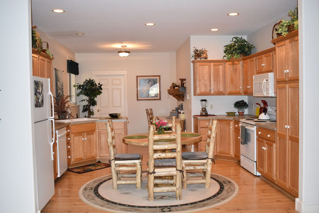 View of kitchen from large family room, comes with stove, refrigerator and basic cooking utensils