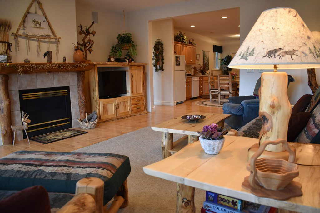View of large family room with fireplace, TV entertainment system and view of kitchen