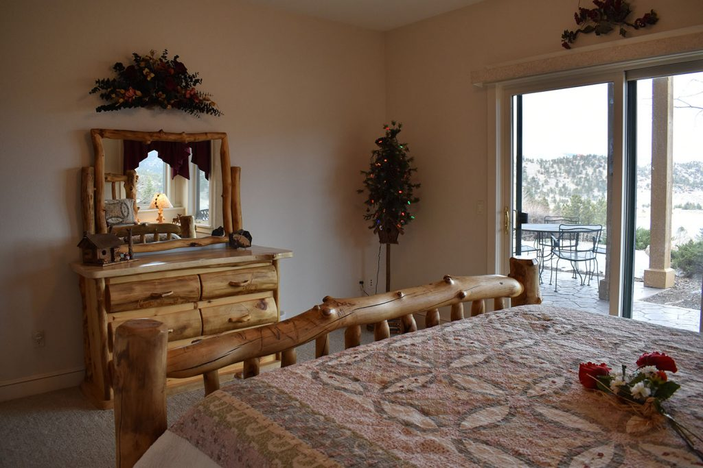 Master bedroom with king bed and rustic wood dresser and mirror